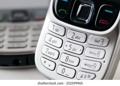 Mobile phone number keypad close up with a second handset in the distance out of focus