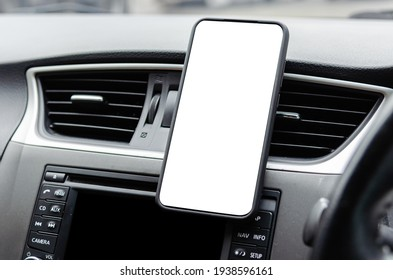 Mobile phone on the car air vent.Blank with white screen.Mock up smart phone in car.