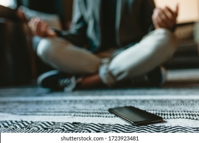 Mobile phone on floor with a businessman meditating in yoga pose in office. Man doing yoga meditation in office lounge.