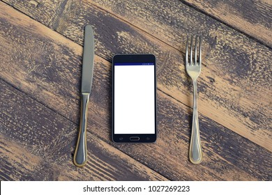 Mobile phone on the menu, with fork and knife. Order online concept. Top view with copy space for text. Blogging concept.