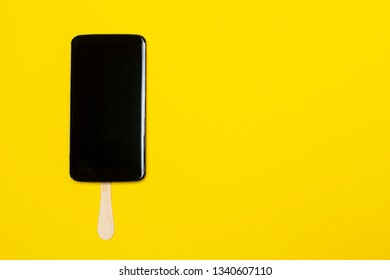 Mobile phone on a stick looks like a delicious chocolate popsicle dessert, with copy space,  on a bright yellow background. Concept of sweet life. Close-up.