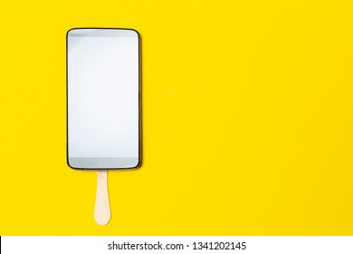 Mobile phone on a stick looks like an appetizing popsicle dessert with frosting, with copy space, on a bright yellow background. The concept of sweet life. Close-up.
