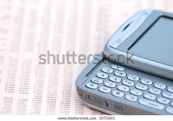 A mobile phone on top of a financial newspaper.
