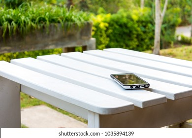 Mobile phone on white wooden table. They are in a garden.