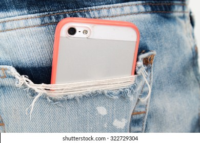 mobile phone in pocket with pink color case.