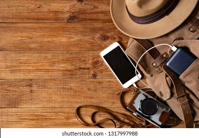Mobile phone with powerbank on wooden table background. Looking image of travelling concept.