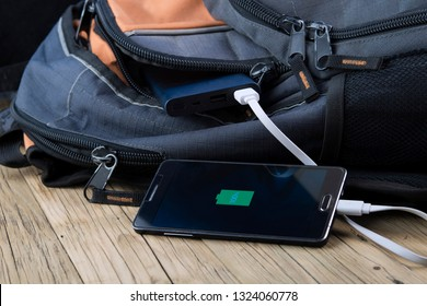 mobile phone with powerbank on wooden table background.