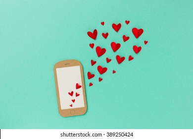 Mobile phone with red hearts flying from the screen - paper illustration image concept for online dating, dating apps