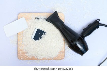 mobile phone in rice and hair dryer on white background