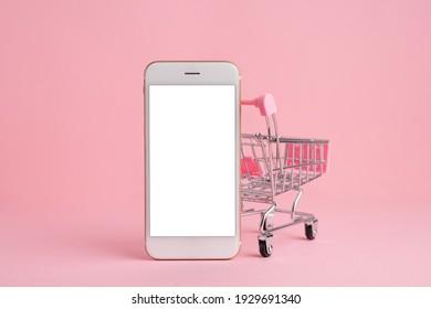 Handy-Bildschirm im Warenkorb-Modell auf rosafarbenem, pastellfarbenem Hintergrund mit Kopienraum , Lieferung und Online-Shopping . Hochwertige Fotoseitenansicht