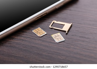 mobile phone and sim card on a wooden background