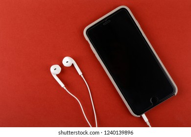 mobile phone smartphone headphones on red background. top view copy space