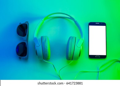 Mobile phone (smartphone), headphones and sunglasses from above (top view, flat lay). Relaxation concept. Colorful (multicolor tonal transitions) background.