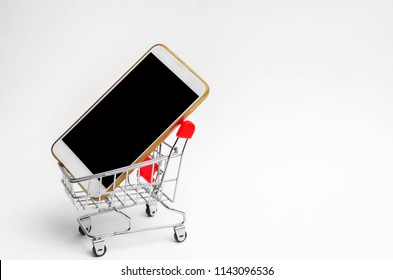 mobile phone in a supermarket trolley. buying and selling a smartphone. online store. consumer credit. isolated white background