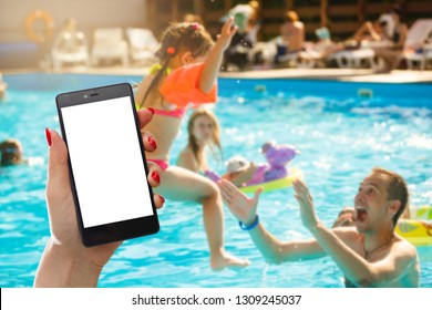 Mobile phone, swimming lessons child as background.