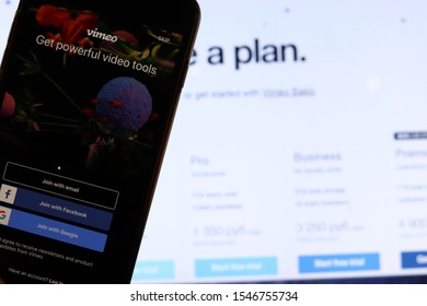Mobile phone with Vimeo logo on screen close up with website on laptop. Blurred background with Vimeo pricing. Los Angeles, California, USA - 27 October 2019, Illustrative Editorial