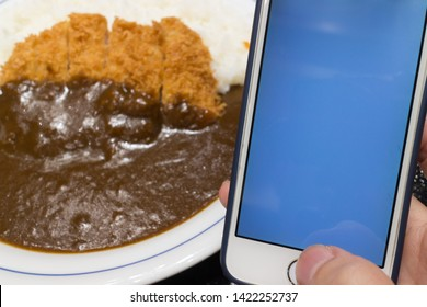 mobile phone white screen with Fried pork Tonkatsu with curry on rice and white dish in the background