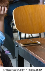 Mobile phone and women on wood table in coffee shop or restaurant