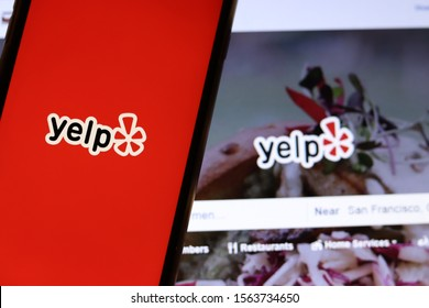 Mobile phone with Yelp icon on full screen close up with website on laptop. Blurred background with Yelp logo. Los Angeles, California, USA - 9 November 2019, Illustrative Editorial