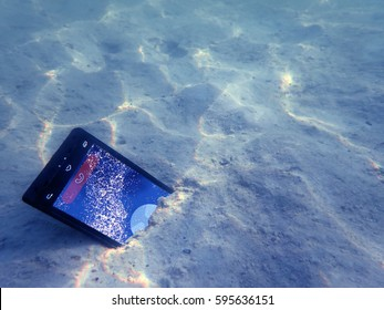 Mobile phones on the sand under the sea water.