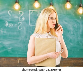 Mobile report concept. Woman with book talking on mobile phone in classroom. Teacher reporting about absent students. Teacher on concentrated face solving problems on phone, chalkboard on background.