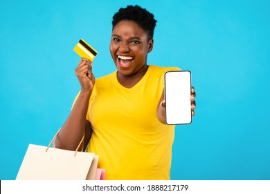 Mobile Shopping Application. Excited Black Woman Showing Smartphone Empty Screen Holding Credit Card Standing Over Blue Studio Background. Female Shopper Recommending App And Phone Banking. Mockup