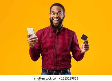 Mobile Shopping Concept. Excited African American Guy Holding Credit Card And Smartphone Posing Standing Over Yellow Background. Studio Shot. Joyful Black Man Making Online Purchase