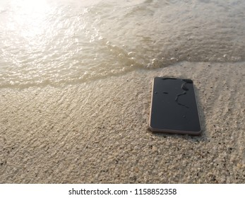 Mobile smart phone on the sandy beach with soft waves of sea background.  Internet of things concept.