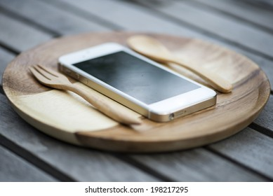 Mobile smart phone served on wood plate. Concept