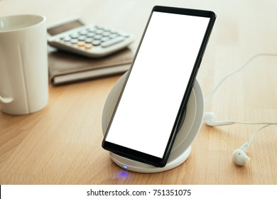 Mobile smartphone is placed on a wireless fast charger. Blank screen with clipping path on screen for your advertising.