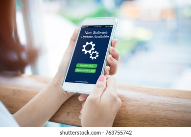 Mobile Software update concept.Close-up of Female hands holidng mobile smart phone