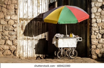 Mobile takeaway with colorful umbrella in the afternoon light in front of an house entrance, Lima, Peru