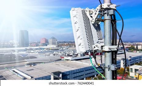 Les antennes de téléphonie mobile des réseaux de téléphonie mobile sur un mât sur le toit diffusant des ondes de signaux au-dessus de la ville par une journée claire et ensoleillée avec ciel bleu et nuages
