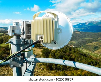 Mobile telephone network base station telecommunication tower with smart cellular antennas radiating and broadcasting strong digital signal waves from view from the top