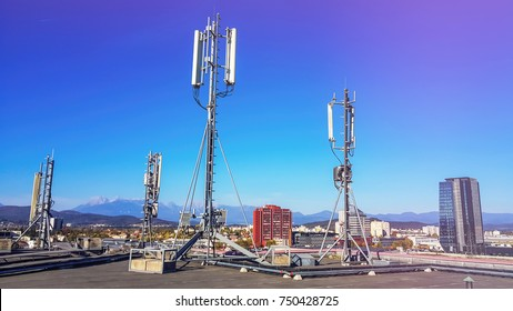 Mobile telephone radio network antennas on the building roof broadcasting signal over the city