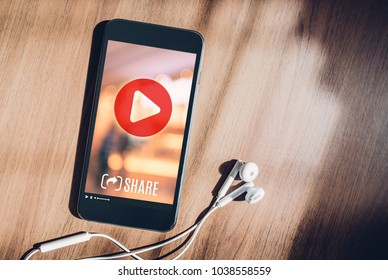 mobile with viral video advertising on phone screen at blur wood table,share video on social media concept,Digital marketing strategy
