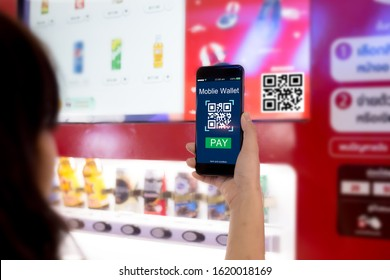 Mobile wallet concept.Woman scanning QR code via mobile phone with Smart Vending machine as background