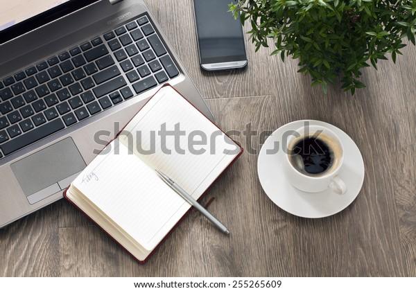 コーヒーと植物を持つ携帯電話の職場