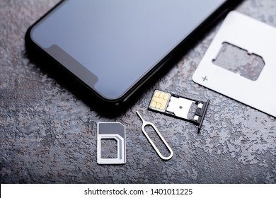 Mobilephone Near Nano Sim Card In The Card Adapter With Eject Pin Over Concrete Background