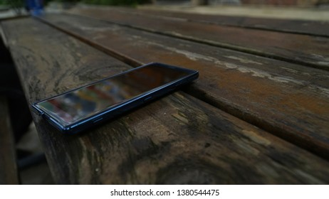 A mobilephone on the wooden table with beautiful reflection
