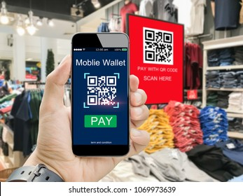 Moblie wallet payment with qr code concept.Hands holding mobile phone on blurred clothing shop in department store as background