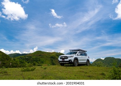 Mocchau, Vietnam - July 17, 2021: Suzuki XL7 car with rooftop tent parked on the hill for camping in a road-trip, Vietnam.