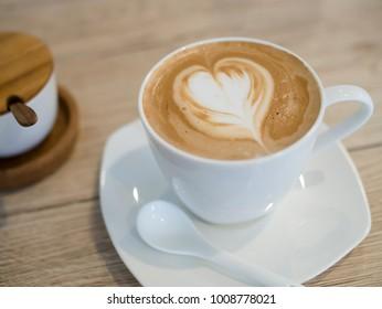 Mocha cappuccino coffee with milk foam designed as heart shape art on wooden table.