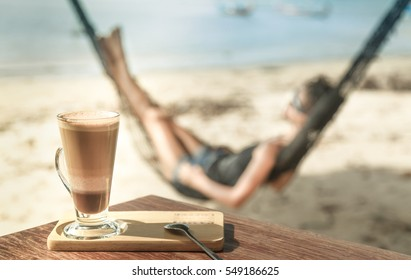 mocha coffee on a table, in the background a woman in a hammock.