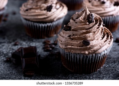 Mocha cupcakes topped with ground coffee and coffee beans. Dark food background with chocolate, coffee beans and whisk
