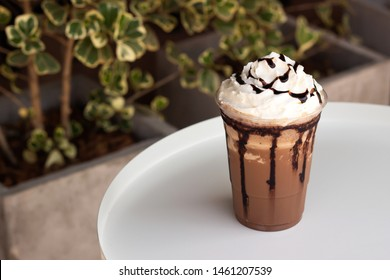 Mocha frappe in plastic cup. Served with whipping cream and chocolate sauce. Freshness drink. Favorite caffeine beverage menu.