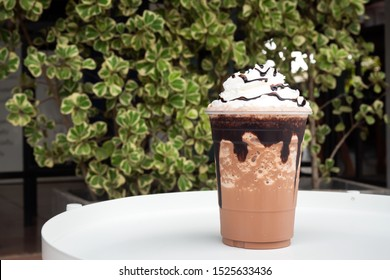 Mocha  frappe in plastic cup with whipping cream and chocolate sauce topping. Sweet favorite coffee menu.