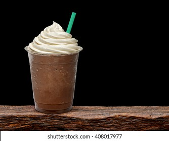 Mocha frappuccino in takeaway cup on wooden table