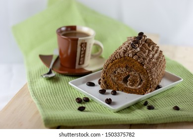Mocha Roll Cake filled and frosted with mocha buttercream served on white plate, green napkin and a cup of coffee