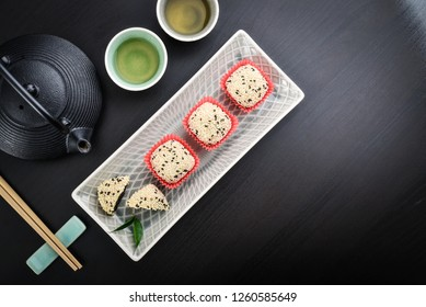 Mochi assortment on plate with chopticks and green tea -  traditional japanese rice dessert, top view